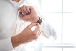 Bräutigam macht sich Uhr an das Handgelenk