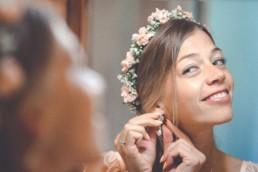 Braut steckt sich ihre Ohrringe in das Ohr