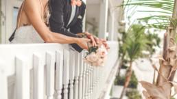 Brautpaar steht mit Brautstrauß am Geländer