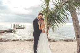 Brautpaar umarmt sich vor Palme am Meer