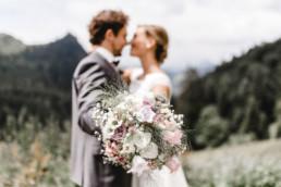 Brautpaar mit Brautstrauß vor Bergkulisse