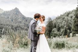 Kopf an Kopf Aufnahme des Brautpaares vor Bergkulisse
