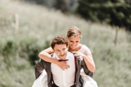 Bräutigam trägt die Braut huckepack