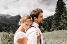 Braut umarmt Bräutigam von hinten vor Bergkulisse