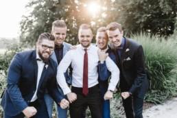Gruppenfoto von männlichen Hochzeitsgästen im gegenlicht