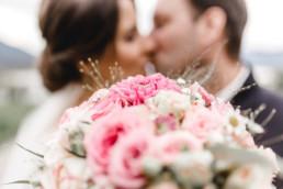 Brautpaar küssend im Vordergrund der Brautstrauß