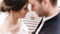 Aufnahme Brautstrauß Brautpaar unscharf im Vordergrund