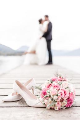 Paar steht küssend unscharf am Steg Brautstrauß im Vordergrund